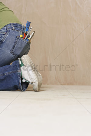 Pocket : Woman with paintbrush and hand tools in back jeans pocket kneeling on floor low section