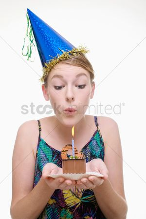 Blowing : Woman with party hat holding a slice of birthday cake and blowing the candle