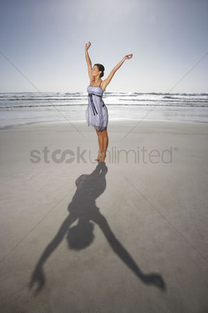 Arm raised : Woman with raised hands standing on beach