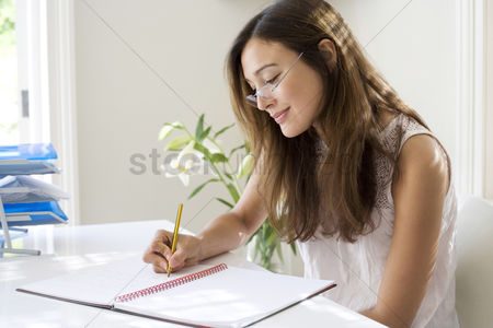 Smiling : Woman working at her desk in a home office