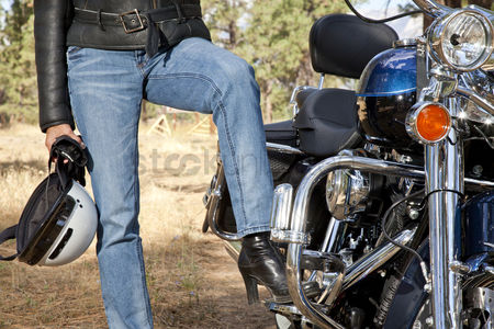 Jacket : Womans leg rests on motorcycle foot rest