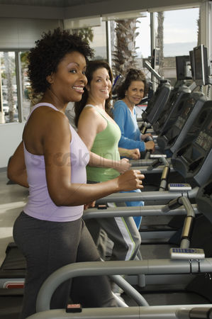 Fitness : Women exercising on treadmills at health club
