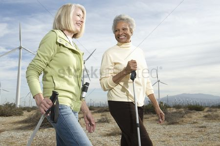 Senior women : Women hiking near wind farm