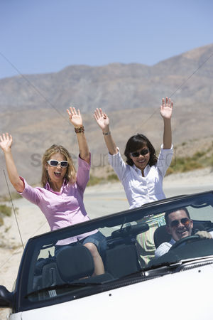 On the road : Women in convertible with hands raised