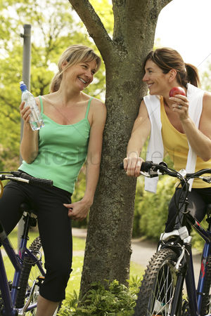 Friends : Women talking while sitting on bicycles
