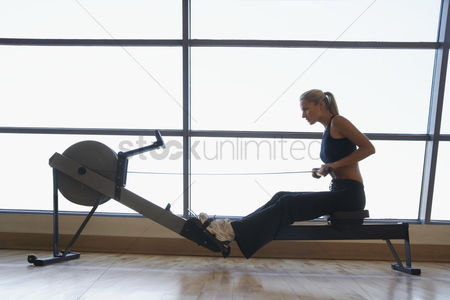 Strength : Women using rowing machine in health club side view