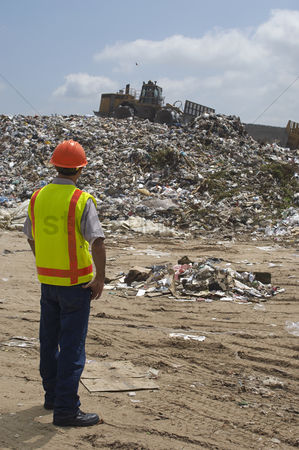 Supervisor : Worker watching digger moving waste at landfill site