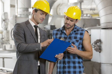 Supervisor : Worker with manager discussing over clipboard in industry