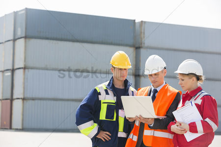 Transportation : Workers discussing over laptop in shipping yard