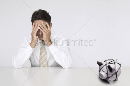 Rope : Worried businessman at table with trapped piggy bank representing financial difficulties