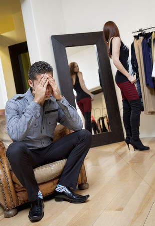 Spending money : Worried young man sitting on armchair with woman in background trying on clothes