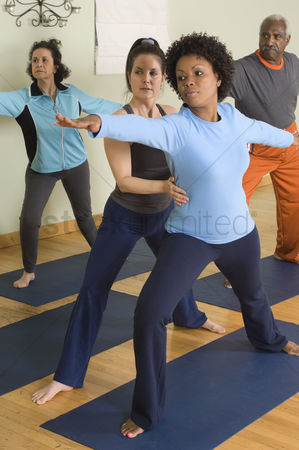 Seniors : Yoga instructor assisting woman in yoga class