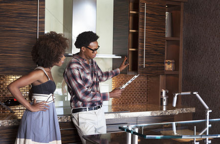 Choosing : Young african american couple in new furnished kitchen choosing materials
