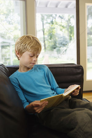 Interior : Young boy  5-6  sitting on sofa reading book