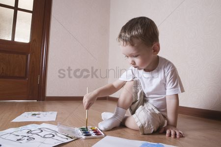 Paint brush : Young boy mixes paints