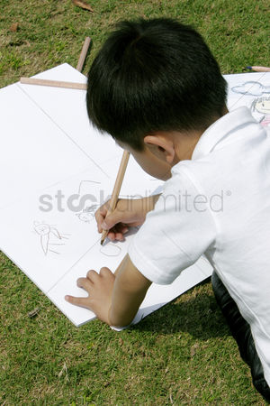 Arts : Young boy painting picture in the park