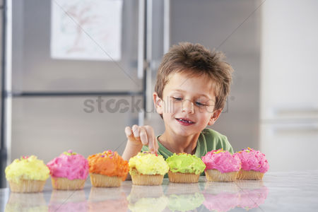 Choosing : Young boy picking decoration off cupcake in kitchen