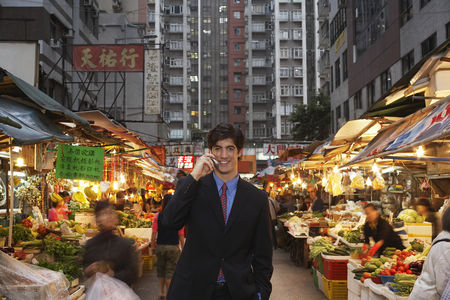 Shopping background : Young business man talking on mobile at street market