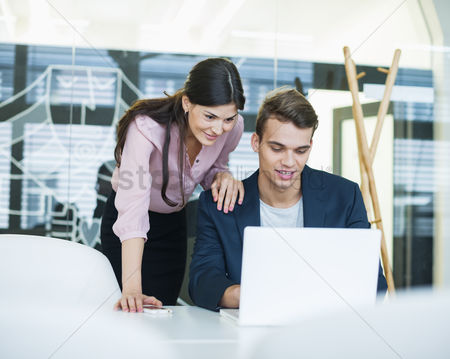 Two people : Young businessman and businesswoman using laptop at table in office