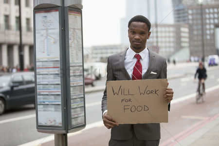 Unemployment : Young businessman holding  will work for food  sign at street