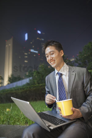 Portability : Young businessman working outdoors and eating
