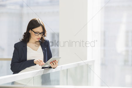 Internet : Young businesswoman using tablet pc in office