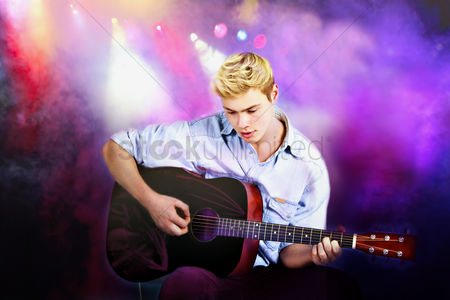Arts : Young caucasian man playing guitar in concert