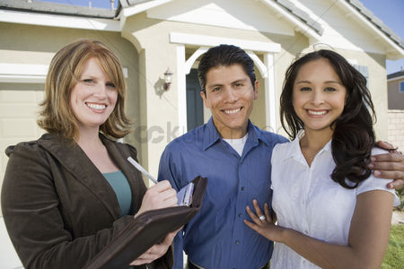 Group portrait : Young couple buying house signing contract