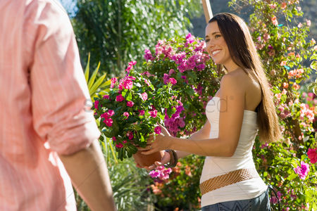 Girlfriend : Young couple choosing potted flowers in outdoors garden centre