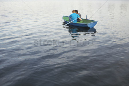 Closeness : Young couple cuddling in rowboat on lake