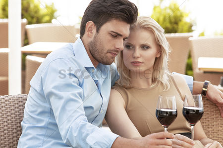 Relationships : Young couple having red wine at outdoor restaurant