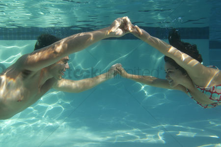 Diving : Young couple holding hands in swimming pool underwater