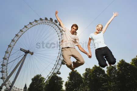Funny : Young couple in park jumping in air in front of london eye portrait low angle view