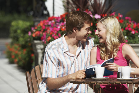 England : Young couple sitting at outdoor cafe laughing and holding guidebook