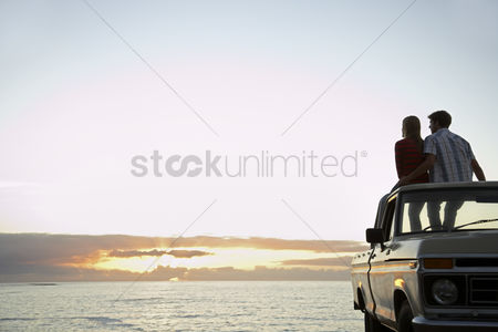Truck : Young couple sitting on van parked in front of ocean back view