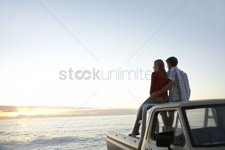 Truck : Young couple sitting on van parked in front of ocean