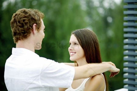 Girlfriend : Young couple smiling while looking at each other
