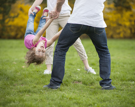 Offspring : Young couple swinging daughter between them