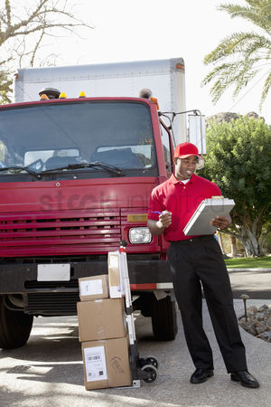 Pushing : Young delivery man looking at delivery list on clipboard with truck in background