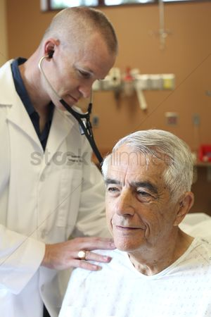 Advice : Young doctor listens to young elderly man s breathing