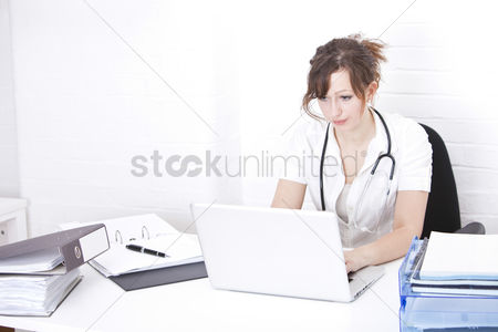 Young woman : Young female doctor using laptop at desk in clinic