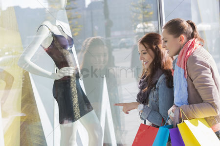 20 24 years : Young female friends window shopping