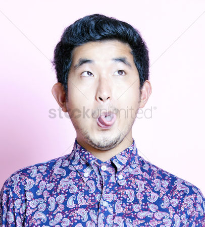Funny : Young geeky asian man in colorful shirt pulling funny face