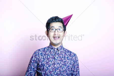 Excited : Young geeky asian man wearing party hat