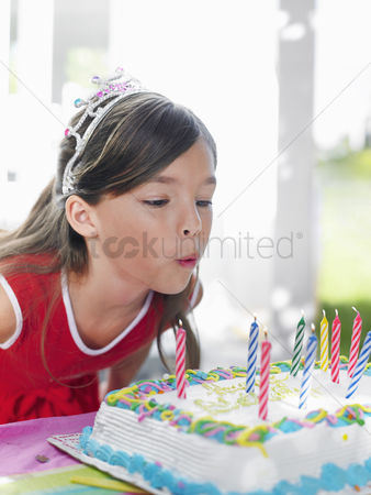 Blowing : Young girl  7-9  blowing out birthday candles close-up