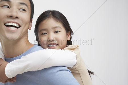 Children playing : Young girl getting piggyback ride with father close-up