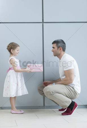 Offspring : Young girl handing present to her father