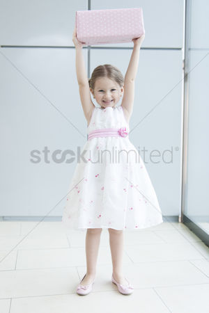 Offspring : Young girl holding gift wrapped box above her head