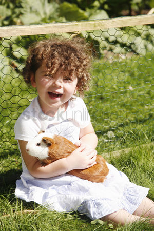 Curly hair : Young girl hugging guinea pig