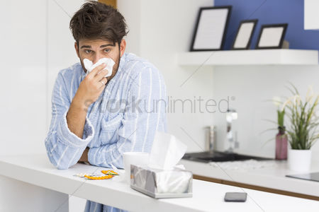 Blowing : Young ill man blowing nose in tissue paper